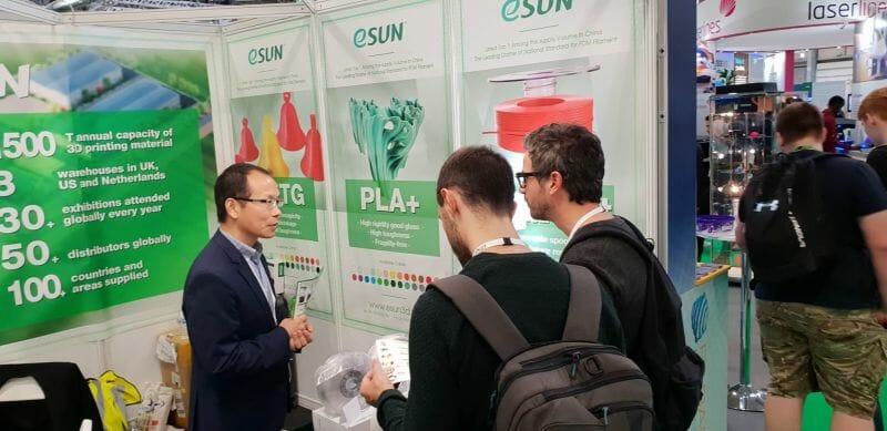 Kevin Yang hablando con los visitantes en el stand de eSUN en TCT 2018 en el R. Unido.